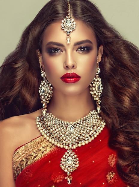 高級ジュエリーセットは、大きなイヤリング、明るいネックレス、頭飾り(ティッカ)で構成されています。完璧で、密度が高く、波打つ、自由に飛ぶ髪と「スモーキーアイ」スタイルのメイク。肖像画をクローズアップ。 Premium写真