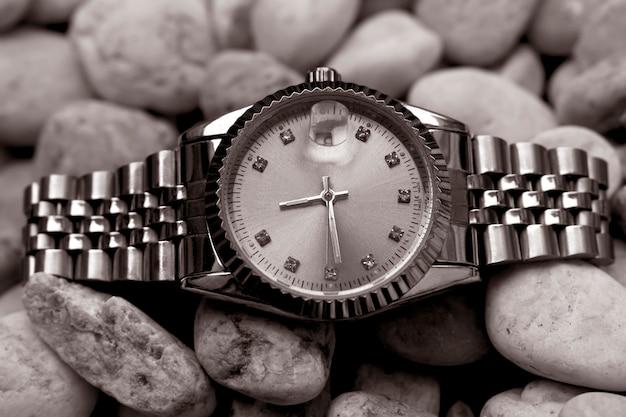 Наручные часы posh, размещенные на блестящем стеклянном полу Premium Фотографии