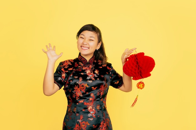 Posing with lantern, smiling, inviting. happy chinese new year. asian young girl portrait on yellow background. copyspace. Free Photo