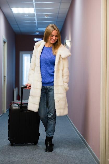 Положительная взрослая женщина стоя в зале с упакованным багажом Premium Фотографии