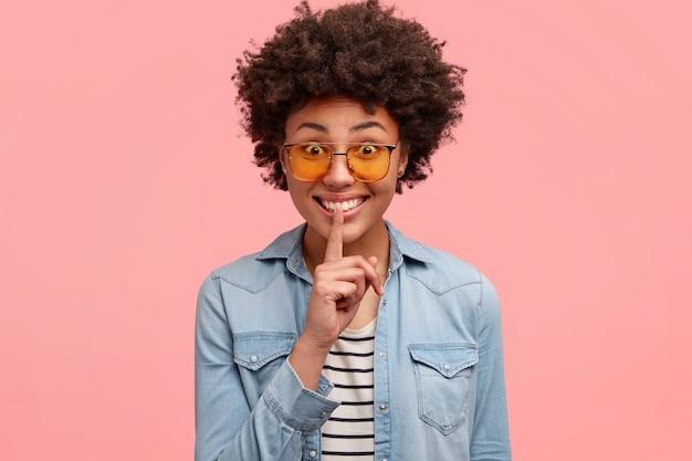 긍정적 인 아프리카 계 미국인 여성은 입술에 검지 손가락을 대고 비밀을 말하면서 자장 기호를 만들고 세련된 옷을 입고 행복한 표정을 짓고 분홍색에 고립 된 곱슬 머리와 하얀 치아를 보여줍니다. 무료 사진
