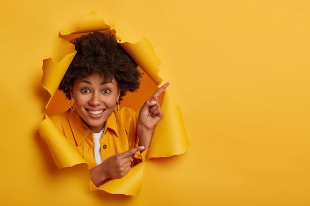 긍정적 인 아프리카 계 미국인 여성은 놀라운 것을 보여주고 검지 손가락으로 옆으로 가리키며 복사 공간을 광고하고 노란색 배경 위에 고립 된 이빨 미소를 가지고 있습니다. 무료 사진