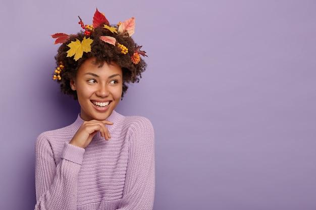Positiva signora afro-americana con foglie di autunno in capelli ricci e bacche mature, indossa un maglione viola lavorato a maglia, messo a fuoco da parte, isolato sopra il muro viola, copia area dello spazio Foto Gratuite