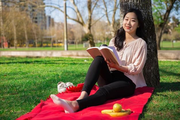 Positive asian girl enjoying interesting novel in park Free Photo