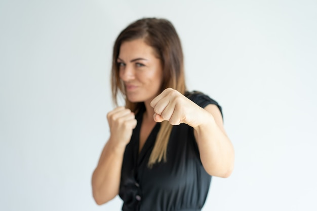 Positive athletic businesswoman punching at camera. Free Photo