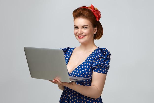 ヴィンテージのドレスと赤い口紅を着てスタジオでポーズをとって、ポータブルコンピューターを使用して高速ワイヤレスインターネット接続を楽しんでいるポジティブで魅力的な若い女性。人 無料写真