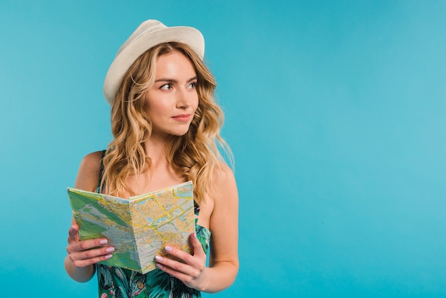 Positive attractive young woman in hat and dress holding map Free Photo