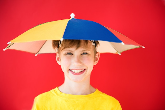 Positive baby boy under colorful umbrella. the concept of protection and forecasting Premium Photo