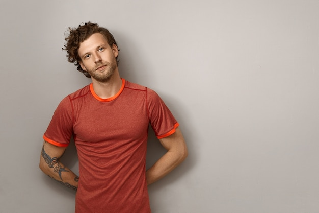 Positive bearded young male runner with curly hairdo and tattoo on muscular arm leaning on blank copyspace wall, keeping hands behind his back. fit athletic macho man posing isolated Free Photo