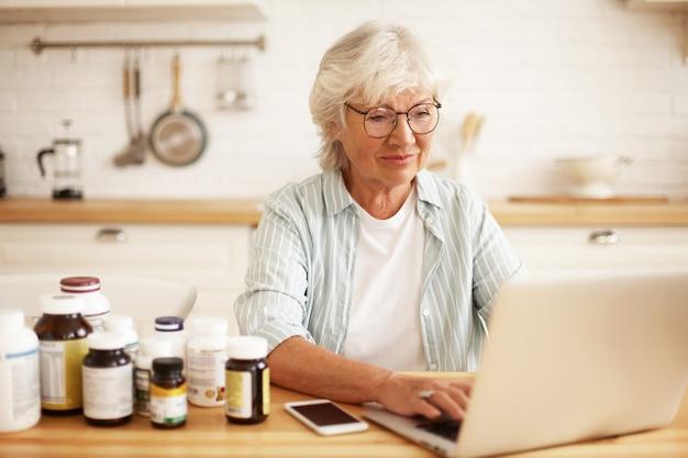 健康的なライフスタイルを選択し、栄養補助食品と一緒にキッチンに座って、ラップトップでキーボード操作し、オンラインストアを介してレビューを入力する眼鏡のポジティブな美しい白髪の女性年金受給者 無料写真