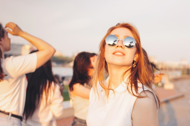 Positive beautiful happy red haired girl in the mirror sunglasses with friends on blue sky background Premium Photo