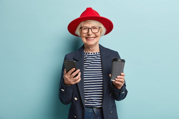 Positive beautiful red haired woman in glasses, uses cell phone, sends message via multimedia application, surfes social networks, has coffee break, holds disposable cup of beverage, isolated on blue Free Photo