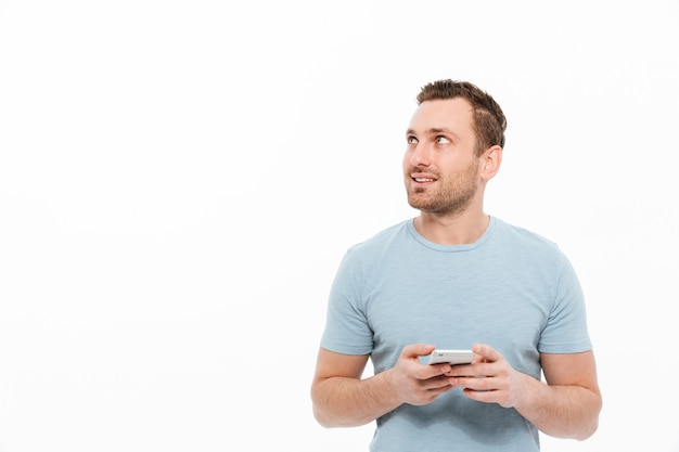 Positive brunette man having bristle smiling and looking aside while using smartphone copy space Free Photo