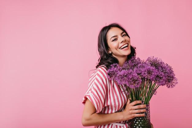 Позитивная брюнетка с ямочками на щеках излучает радость. снимок милой кудрявой дамы с прекрасными огромными фиолетовыми цветами. Бесплатные Фотографии