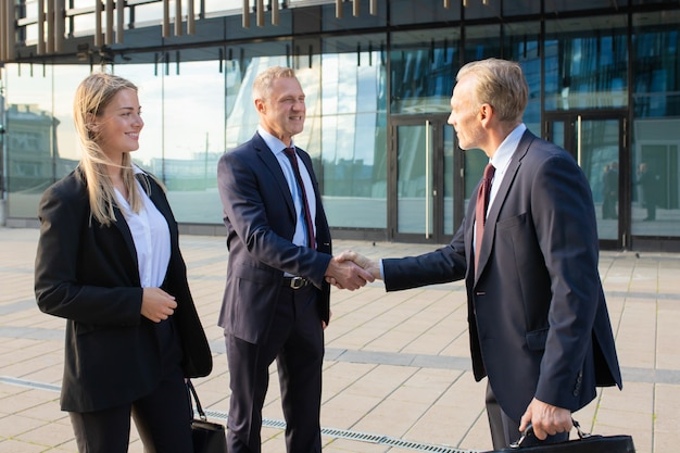 Positive business partners meeting at office building, shaking hands with each other. side view, medium shot. corporate communication or handshake concept Free Photo