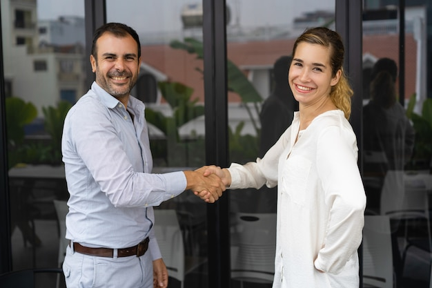Positive business partners shaking hands Free Photo