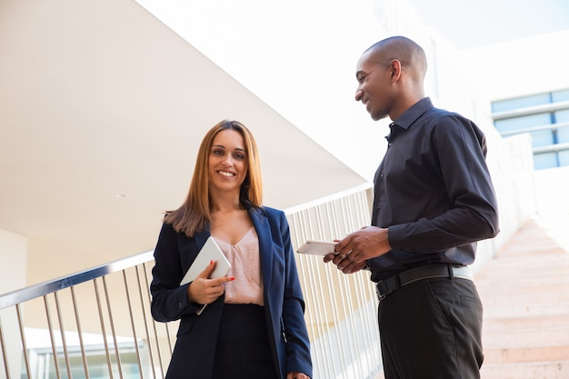 Positive business people chatting and holding tablets on stairs Free Photo