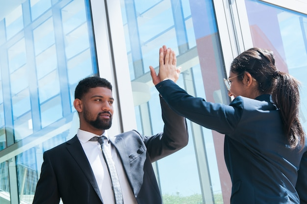Positive business people high fiving outdoors Free Photo
