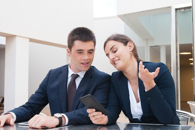 Positive business woman showing smartphone screen to colleague Free Photo
