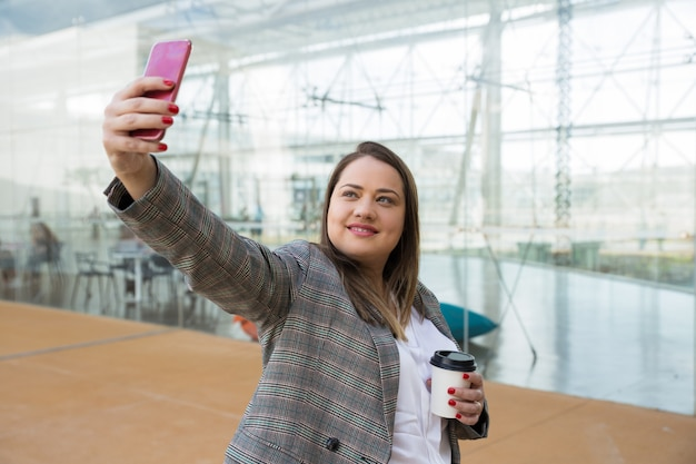 Positive business woman taking selfie photo on phone outdoors Free Photo
