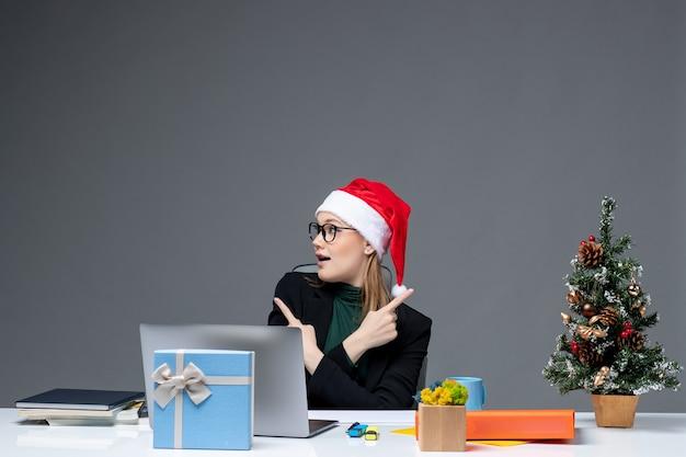 Donna d'affari positiva con cappello di babbo natale seduto a un tavolo con un albero di natale e un regalo su di esso su sfondo scuro Foto Gratuite