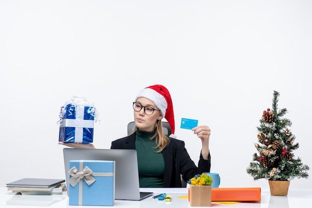 Positive business woman with santa claus hat and wearing eyeglasses sitting at a table holding christmas gift and bank card on white background Free Photo