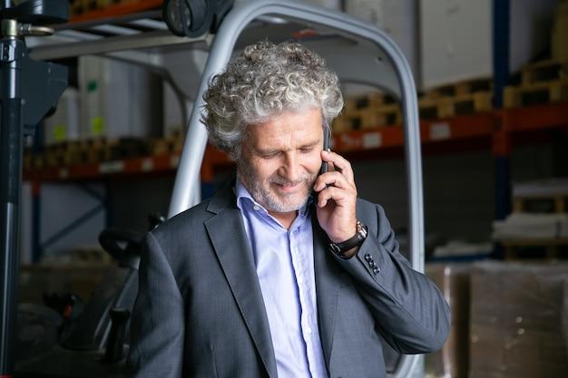 Uomo d'affari positivo in piedi vicino al carrello elevatore in magazzino e parlando al cellulare. ripiani con merci in background. concetto di business o logistica Foto Gratuite