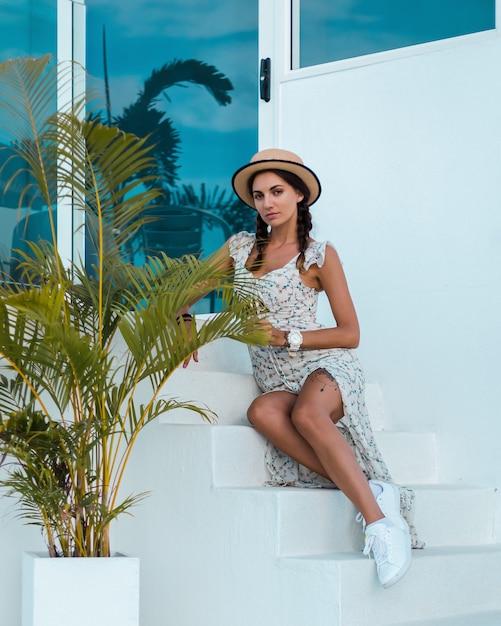 Donna calma positiva in abito estivo leggero, cappello di paglia, posizione tropicale Foto Gratuite
