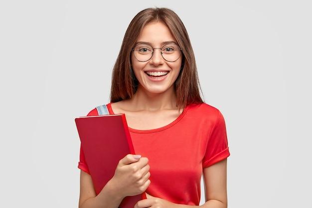 魅力的な笑顔のポジティブな白人の女の子、赤いtシャツを着て、教科書を持って、白い壁にモデルを置き、勉強する気分があり、視力の良い眼鏡をかけています。若者、学習の概念 無料写真