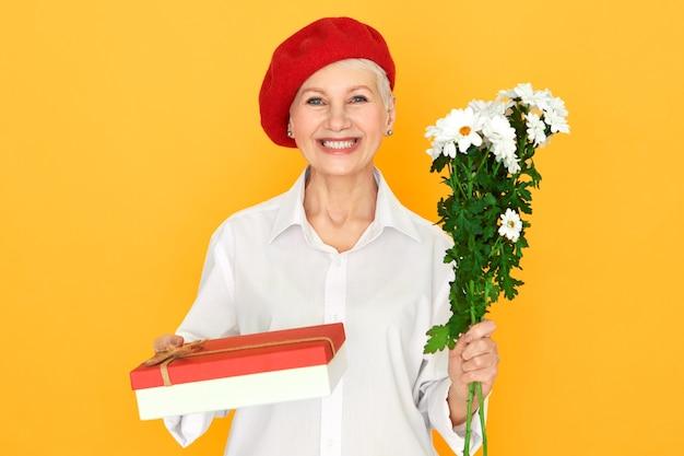 생일 선물을 받고, 기념일을 축하하고, 흰색 데이지와 사탕 상자를 잔뜩 들고, 빛나는 행복한 미소로 카메라를보고 긍정적 인 매력적인 중간 나이 든 여자. 축하 개념 무료 사진