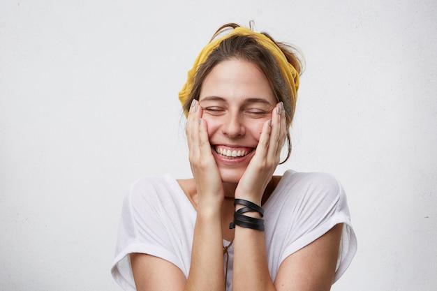 陽気な陽気な女性が頬に手をかざし、笑顔が広く、気分が良い喜びで目を閉じている 無料写真