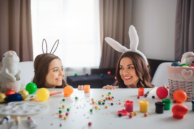 Positive cheerful mother and daughter prepare for easter. they play and hide behind table in room. mother and daughter look at each other and smile. they wear bunny ears. Premium Photo
