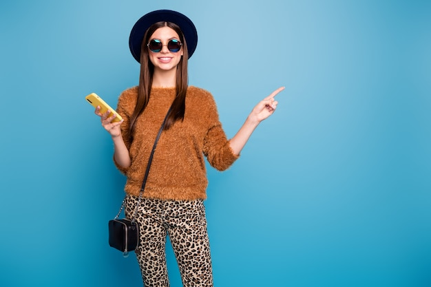 Positive cheerful student girl use smartphone repost ads promotion point index finger copyspace wear retro hat handbag brown sweater casual trousers isolated over blue color wall Premium Photo