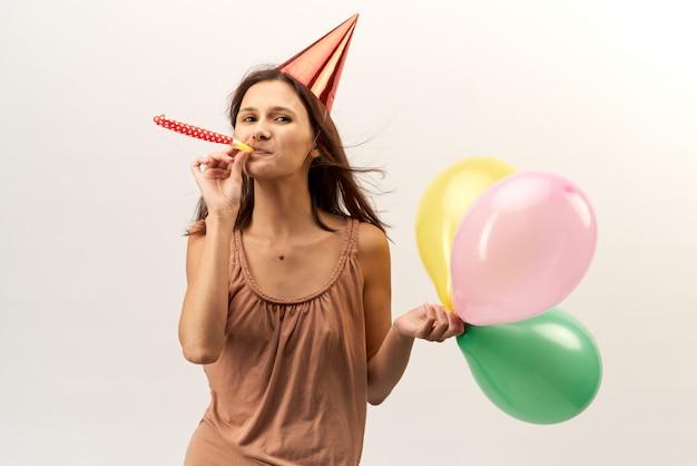 파티 모자와 트럼펫과 Baloons 긍정적 인 명랑 소녀 긴 머리를 흐르는와 초상화에 대 한 포즈. 격리 된 흰 배경에 스튜디오 초상화입니다. 휴일, 생일, 업적. 프리미엄 사진