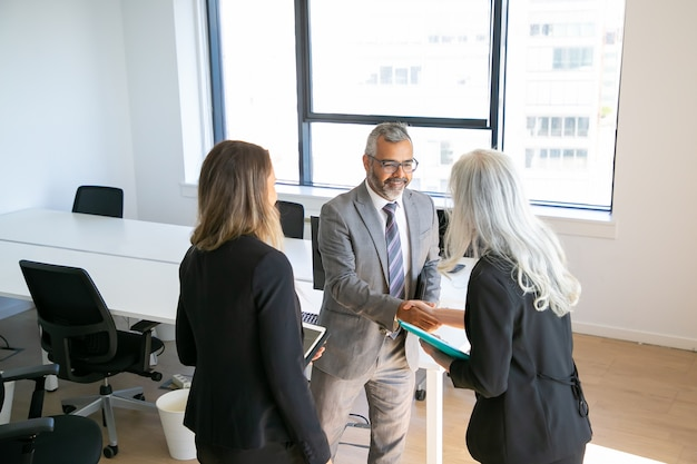 Positive confident business partners ending meeting with handshake, in office and discussing collaboration. high angle. communication or partnership concept Free Photo