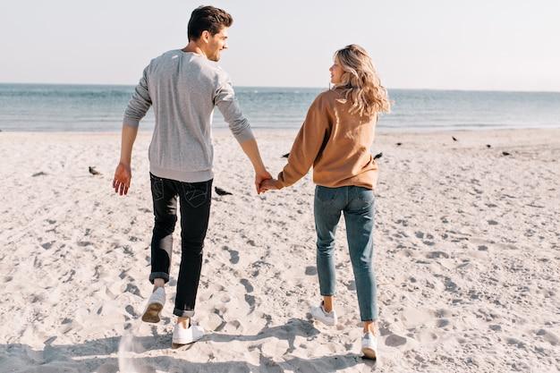 미소와 함께 바다를 실행하는 긍정적 인 커플. 해변에서 휴식하는 동안 남자 친구와 손을 잡고 예쁜 여자의 야외 초상화. 무료 사진