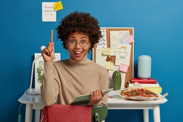 Positive curly woman writes down notes in diary, creats funny story, wears glasses with good lense, raises hand with pen Free Photo
