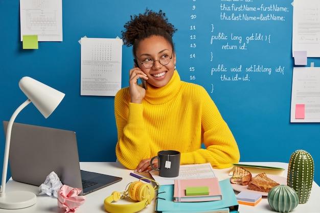 La ragazza dalla pelle scura positiva fa una telefonata, discute il miglioramento e lo sviluppo del progetto di business, vestita con un maglione giallo, guarda da parte, pone su sfondo blu Foto Gratuite