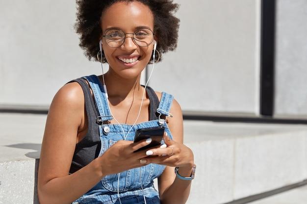 歯を見せる笑顔のポジティブなダークスキンの女性、デジタルセルラーでオーディオを聴き、お気に入りの曲を聞いて幸せで、純粋な音を楽しみ、丸い眼鏡とカジュアルな服を着て、外でポーズをとる 無料写真