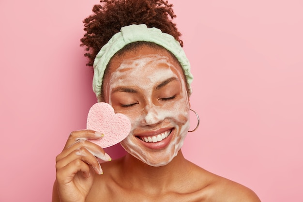 Positive dark skinned woman with afro combed hair, wears headband, cares about facial skin, wipes cheek with cosmetic sponge, keeps eyes shut with pleasure Free Photo
