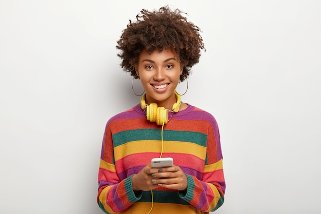 줄무늬 화려한 스웨터를 입은 긍정적 인 기쁘게 아프리카 계 미국인 여자, 헤드폰에 연결된 현대 핸드폰 보유, 인터넷 서핑 무료 사진