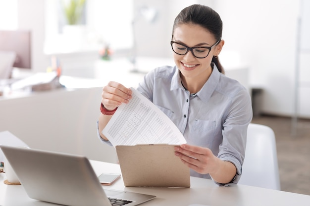 笑顔を保ちながら職場に座って両手で書類を持って喜んでいる前向きな秘書 Premium写真