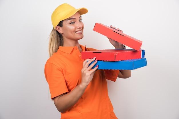 ピザの箱を開けるポジティブデリバリーの女性。 無料写真