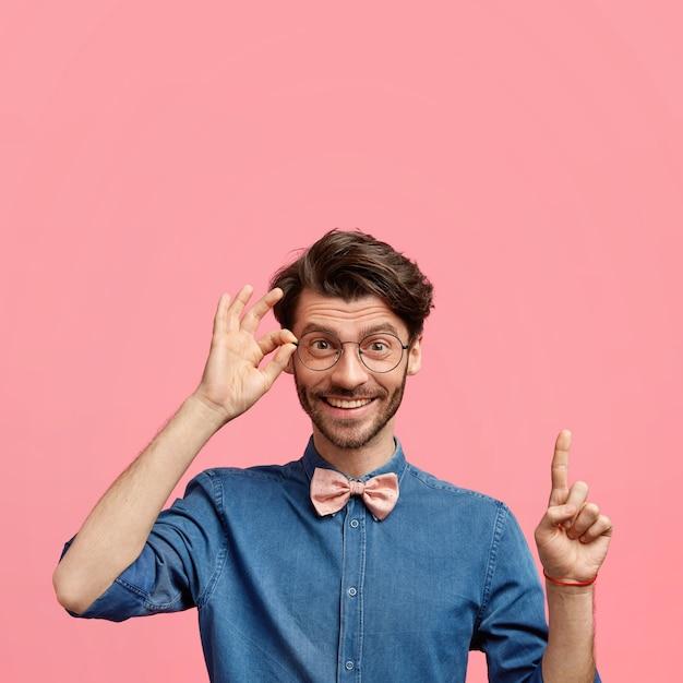 Il giovane maschio positivo ed elegante con l'acconciatura alla moda e la barba incolta, vestito con una camicia di jeans con papillon, ha un'espressione gioiosa, punta verso l'alto contro il muro rosa, tiene la mano sul bordo degli occhiali Foto Gratuite