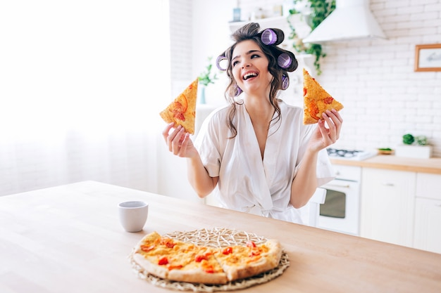 Positive emotional young carefree housekeeper in kitchen. holding two slices of pizza and smile. cup on table. alone in kitchen. life without work. Premium Photo