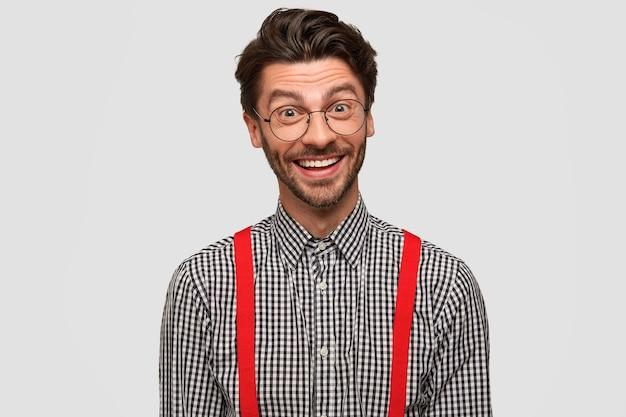 Concetto di emozioni positive. bell'uomo barbuto con un ampio sorriso luminoso, di buon umore perché ha trovato un buon lavoro ben pagato Foto Gratuite