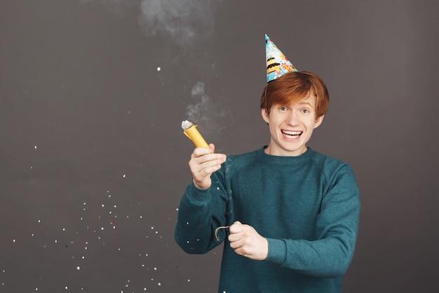 Позитивные эмоции. портрет молодой рыжий парень в зеленом свитере с удовольствием на день рождения с семьей Бесплатные Фотографии