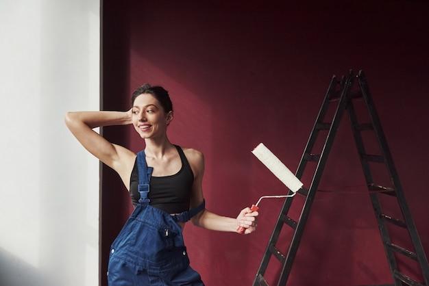 ポジティブな感情。部屋の新しい家に壁紙を接着することにした若い主婦 無料写真