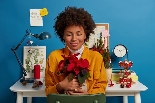 La ragazza etnica positiva gode del piacere di essere a casa, abbraccia un vaso con un bel fiore rosso, indossa una giacca di jeans gialla, posa sul desktop e interni accoglienti decorati Foto Gratuite