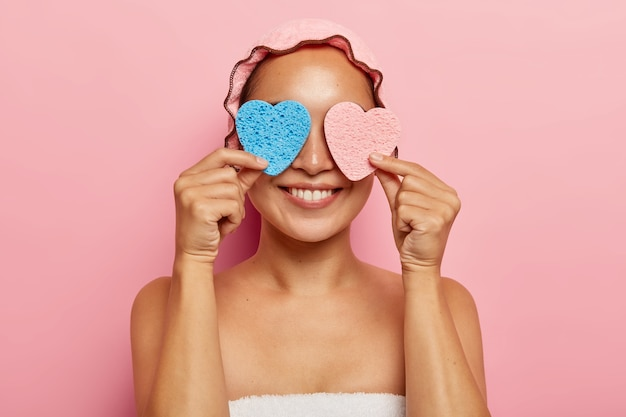 Positive ethnic woman covers eyes with two sponges, has beauty treatments, smiles happily, wears shower cap on head, has healthy skin, isolated on pink wall. purification, face care concept Free Photo